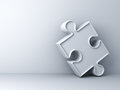 White jigsaw puzzle piece on white wall Royalty Free Stock Photo