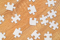 White jigsaw puzzle pieces scattered on wooden table Royalty Free Stock Photo