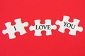 White jigsaw puzzle with a written word I Love You on a red background Royalty Free Stock Photo