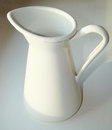 White jug for watering flowers on a windowsill Royalty Free Stock Photography