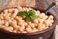 White kidney beans in a brown pot macro and bread Royalty Free Stock Photo