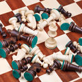 White king and scattered chess pieces on chessboard Stock Photography