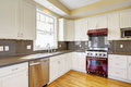 White kitchen with burgundy stove and grey counter tops bright room hardwood floor cabinets Royalty Free Stock Image