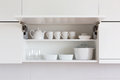 White kitchenware opened cupboard with inside Royalty Free Stock Images