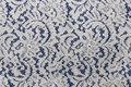 White lace fabric with floral pattern on blue Royalty Free Stock Photo