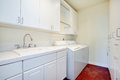 White laundry room with a red floor and wooden storage combination Royalty Free Stock Image