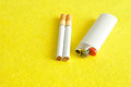 A white lighter with two cigarettes Royalty Free Stock Photo