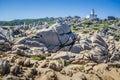 White lighthouse of Capo Testa in north Sardinia, Hudge Granite Rocks in front Royalty Free Stock Photo
