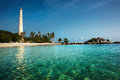 White lighthouse standing on an island in Belitung at daytime. Royalty Free Stock Photo