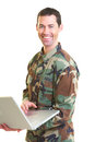 White male in army uniform on lap top smiling Stock Photo