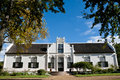 White manor house on a winefarm framed with autumn color leaves against blue sky in the western cape south africa Stock Images