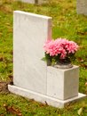 White marble gravestone from behind with pink flowers cemetery Royalty Free Stock Photo