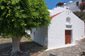 White mediterranean church and an old tree in lindos at rhodes island in the summer noon besides it Royalty Free Stock Photo