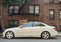 White mercedes e parked in front of a red brick building Royalty Free Stock Images
