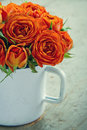 White mug with a bouquet of orange roses on green vintage wooden background Stock Image