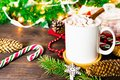 White mug of cocoa with marshmallows, lollipops, fir cones, Christmas tree branch, garland and snowflake on wooden table Royalty Free Stock Photo