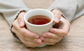 White mug in hands of tea hand on background table Royalty Free Stock Photography