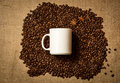White mug lying on pile of roasted coffee beans on linen cloth Royalty Free Stock Photo