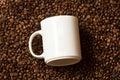 White mug lying on roasted coffee beans Royalty Free Stock Photo