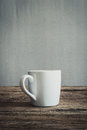 White mug on wooden tabletop against grunge wall vintage tone Royalty Free Stock Images