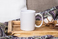 White mug on a wooden tray, the Mockup. Cozy home, linen and wool decorations Royalty Free Stock Photo