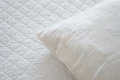 White natural textiles pillow lies on the bed cover made of Royalty Free Stock Images