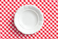 White old plate on checkered napkin Royalty Free Stock Photo