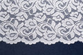 White openwork lace with floral pattern on a blue background. Royalty Free Stock Photo