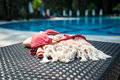 A white and orange Turkish towel, bikini top, and white seashells on rattan lounger with blue a swimming pool as background. Royalty Free Stock Photo