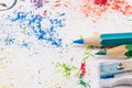 White paper covered in colored pencils sharpening leftovers Royalty Free Stock Photo