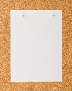 White paper note sheet with white push pin on cork board Royalty Free Stock Photo
