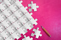 White paper puzzle pieces on pink leather background.jpg Royalty Free Stock Photo