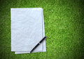 White paper sheet on green grass background Royalty Free Stock Photo