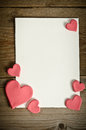 White paper with small pink hearts on a wooden background Royalty Free Stock Photo