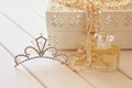 White pearls necklace diamond tiara and perfume on toilette tab bottle table selective focus vintage filtered Stock Image