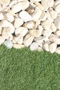 White pebbles against a grassy verge Royalty Free Stock Images