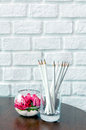 White pencils in a glass beside beautiful flower glass jar on the wooden table and brick wall background with light from Royalty Free Stock Photos