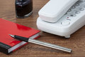 White phone and fountain pen on wooden texture a an inkwell a red notebook a imitating a desk Stock Photo