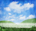 White picket fence a with a blue cloudy sky and green hills Royalty Free Stock Photo