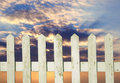 White picket fence with clouds Royalty Free Stock Photo