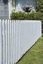 White picket fence detail of next to lawn in front of house Royalty Free Stock Photo