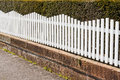 White picket fence next to pathway with bush behind Stock Photo