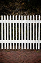 White Picket Fence with Red Brick Sidewalk and Tre Royalty Free Stock Photo