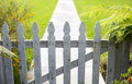 White picket fence and a walkway Stock Photo