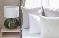 White pillows on modern white bed with modern lamp Royalty Free Stock Photo