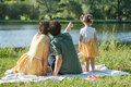 On white plaid sit back parents. Look at the pond. Dad points a finger into the distance. Royalty Free Stock Photo