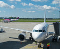 White plane docking in the airport runway and wizz air aircraft in background Royalty Free Stock Photo