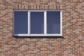 White plastic window and red  brick wall Royalty Free Stock Photos