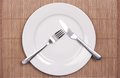 White plate on bamboo mat a with knife and fork Royalty Free Stock Images
