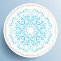 White plate with blue floral ornament on light background Royalty Free Stock Photos